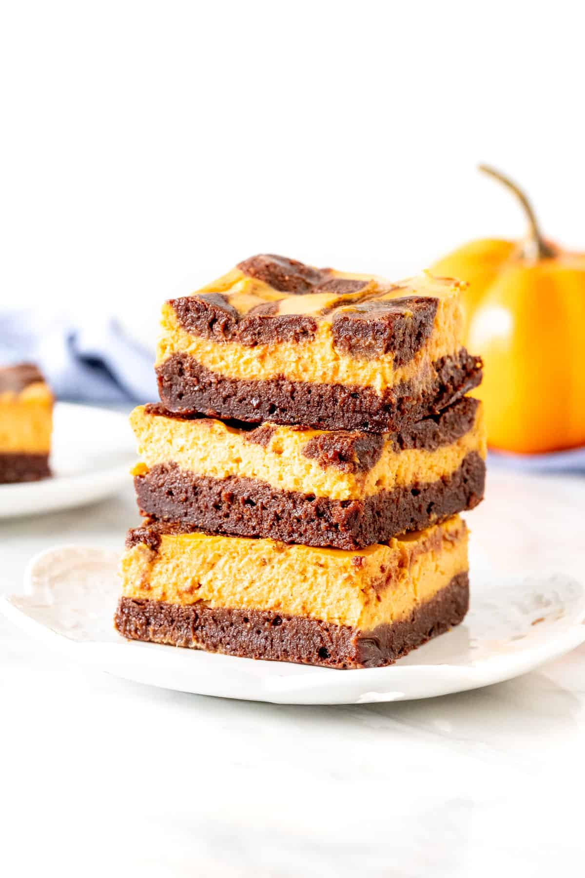 3 pumpkin cheesecake brownies stacked on top of each other.