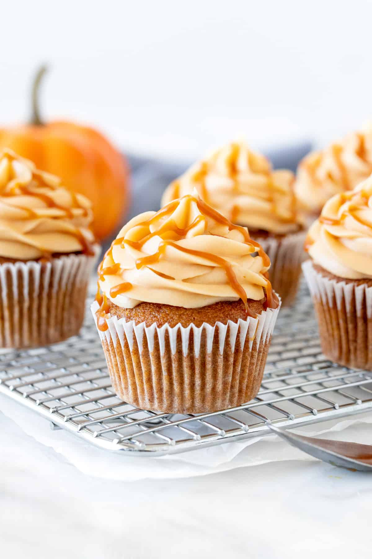 Pumpkin cupcakes with caramel cream cheese frosting on a wire rack.