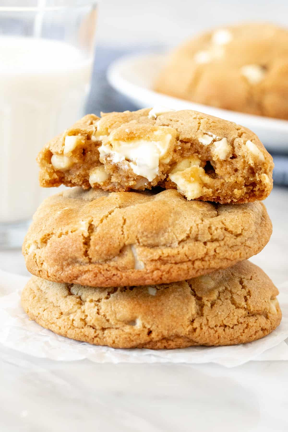 Stack of bakery-style white chocolate macadamia cookies with top cookie broken in half.