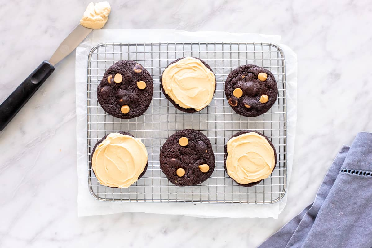 6 chocolate cookies with peanut butter frosting on a cooling rack