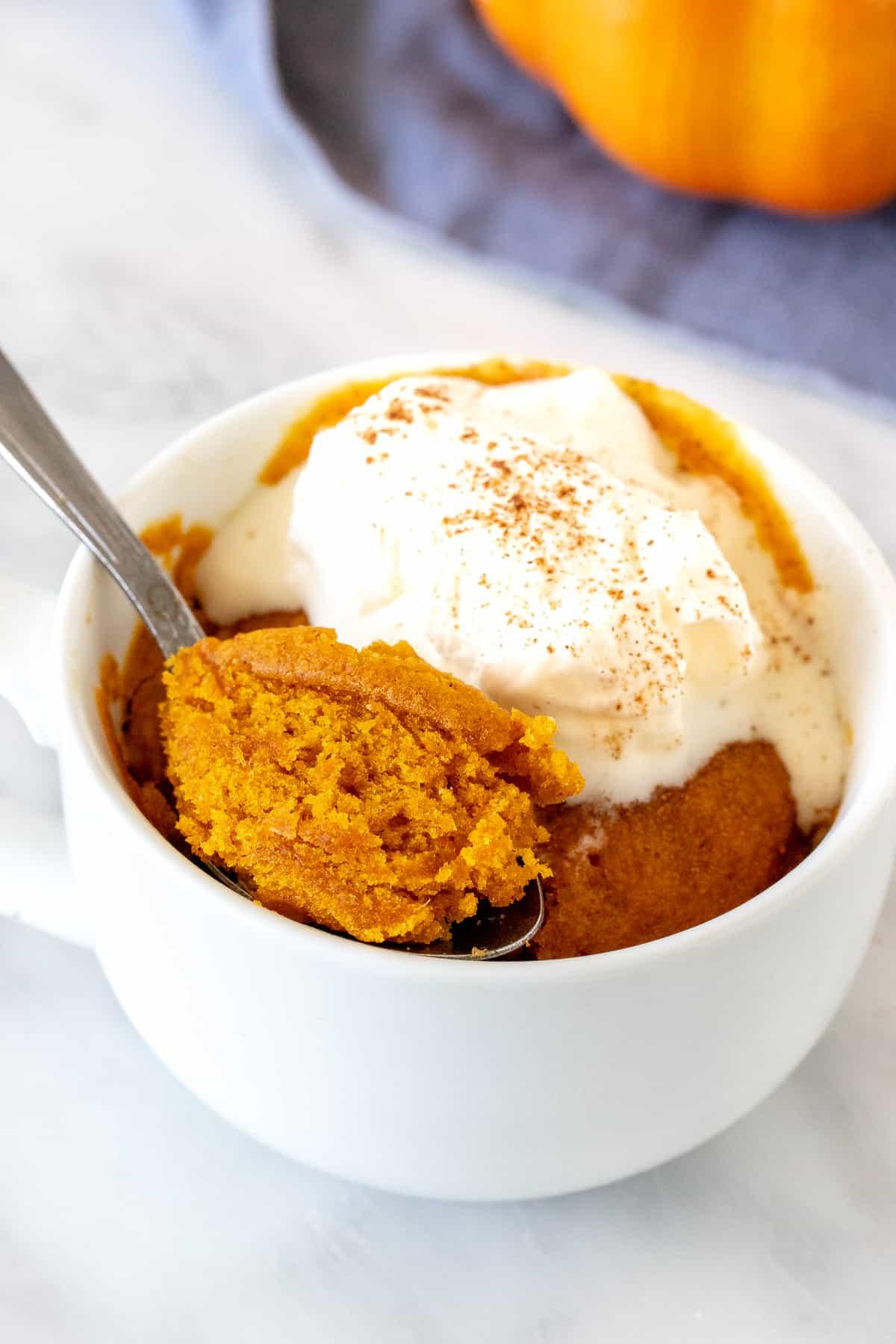 Pumpkin mug cake topped with whipped cream