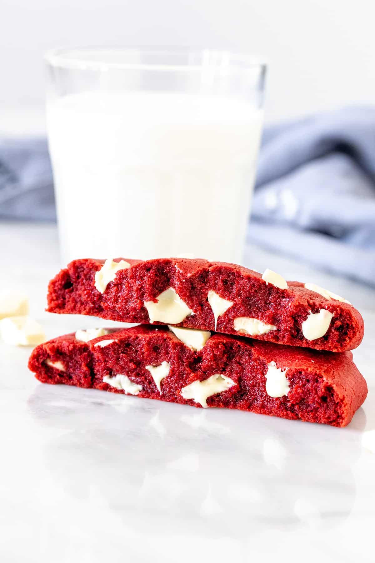 Single serving red velvet cookie, broken in half with a glass of milk